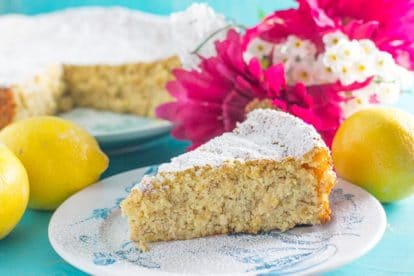 slice of lemon almond cake on a blue and white plate; pink and white flowers in background along with lemons