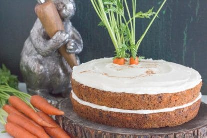 low FODMAP carrot cake with cream cheese frosting and bare sides on a wooden plate with decorative bunny in the background