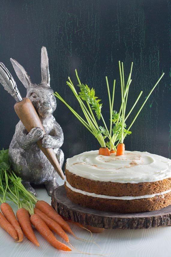 low FODMAP carrot cake with cream cheese frosting on a wooden plate with decorative bunny in the background.-3