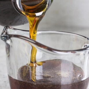 maple syrup pouring into a glass pitcher