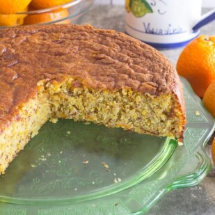 clementine almond cake on a depression glass green plate; stone background
