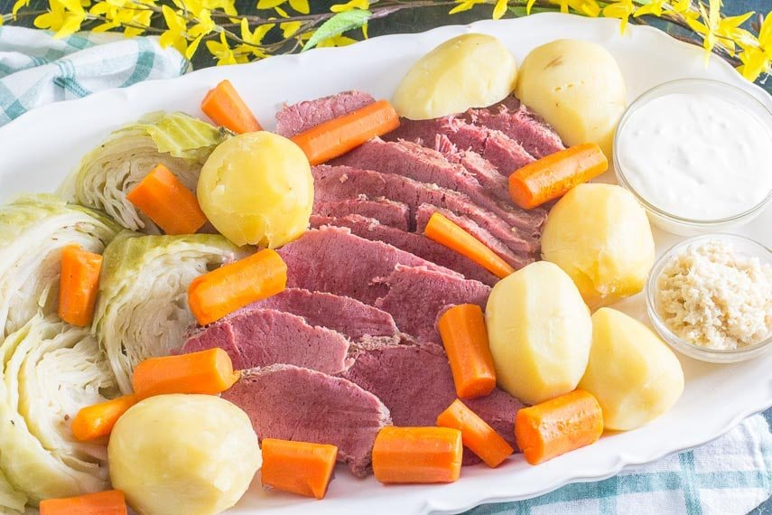 oval white platter of corned beef, cabbage, potatoes and carrots