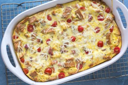 overhead shot of ham and cheese strata in a white casserole dish on a rack against a blue background
