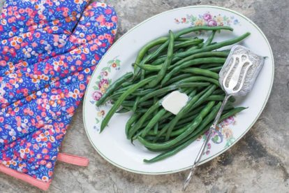 perfect steamed green beans on an oval platter with a pat of melting butter