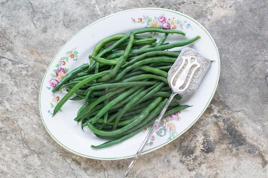 perfect steamed green beans on an oval platter with silver server