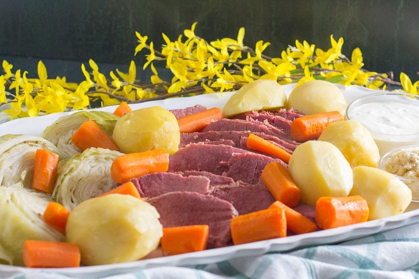 platter of corned beef, cabbage, potatoes and carrots with flowers in background