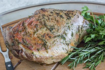 roast leg of lamb on a cutting board with frsh herbs alongside