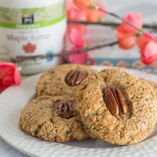 Gluten-free Maple Pecan Scones on a white plate with spring blossoms in background