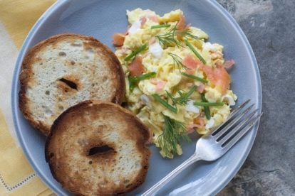scrambled eggs with smoked salmon, cream cheese, chives nad dill on a crackled plate with toasted bagels-2