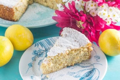 slice of lemon almond cake on a blue and white platye; pink and white flowers in background along with lemons