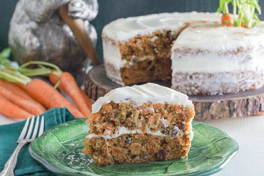 slice of low FODMAP carrot cake with cream cheese frosting on green plate with carrots and whole cake in background