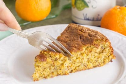 slice of clementine almond cake on a white plate; fork cutting into it