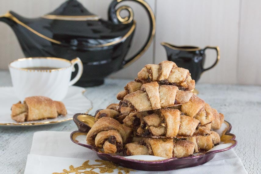 tall pile of low FODMAP rugelach on a decorative plate with a black teapot in background