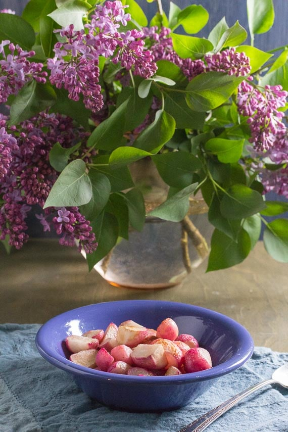 vertical image of bouquet of lilacs with sauteed radishes in foreground in blue bowl