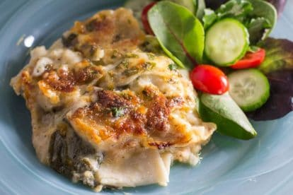 Chicken & Spinach Lasagna Bake on a blue plate with salad alongside