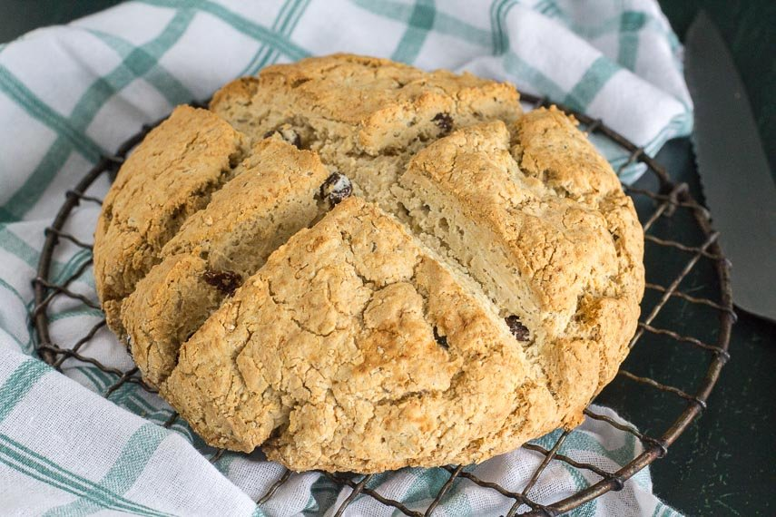 whole Irish soda bread on round cooling rack with green and white kitchen cloth