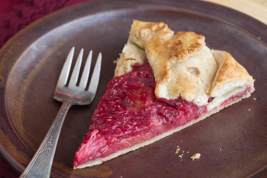 Rhubarb Raspberry Crostata slice on brown ceramic plate with silver fork