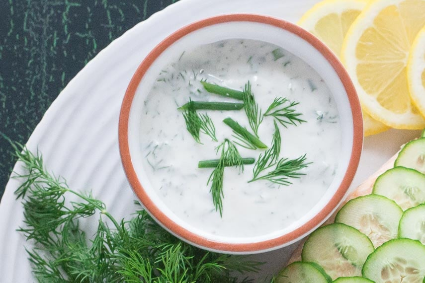 Yogurt dill sauce in small white bowl with fresh dill and chives