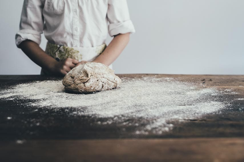 Female baker working with heavily floured dough on wooden surface; Choosing a Low FODMAP All-Purpose Flour