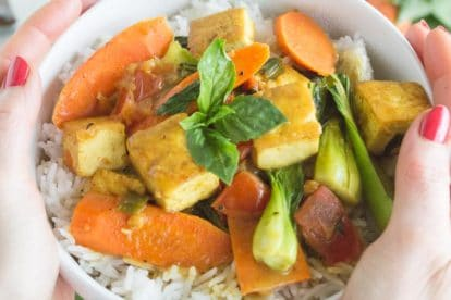 coconut tofu curry in white bowl with basmati rice, held by a women's hands