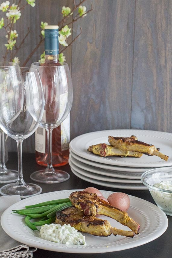 lamb chops vertical image on white plate with green beans and steamed potatoes. Wine bottle and glasses in background.