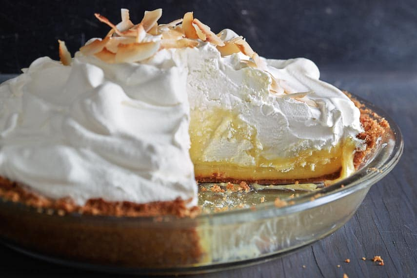 Coconut-Lime Cream Pie in a glass dish against a dark background