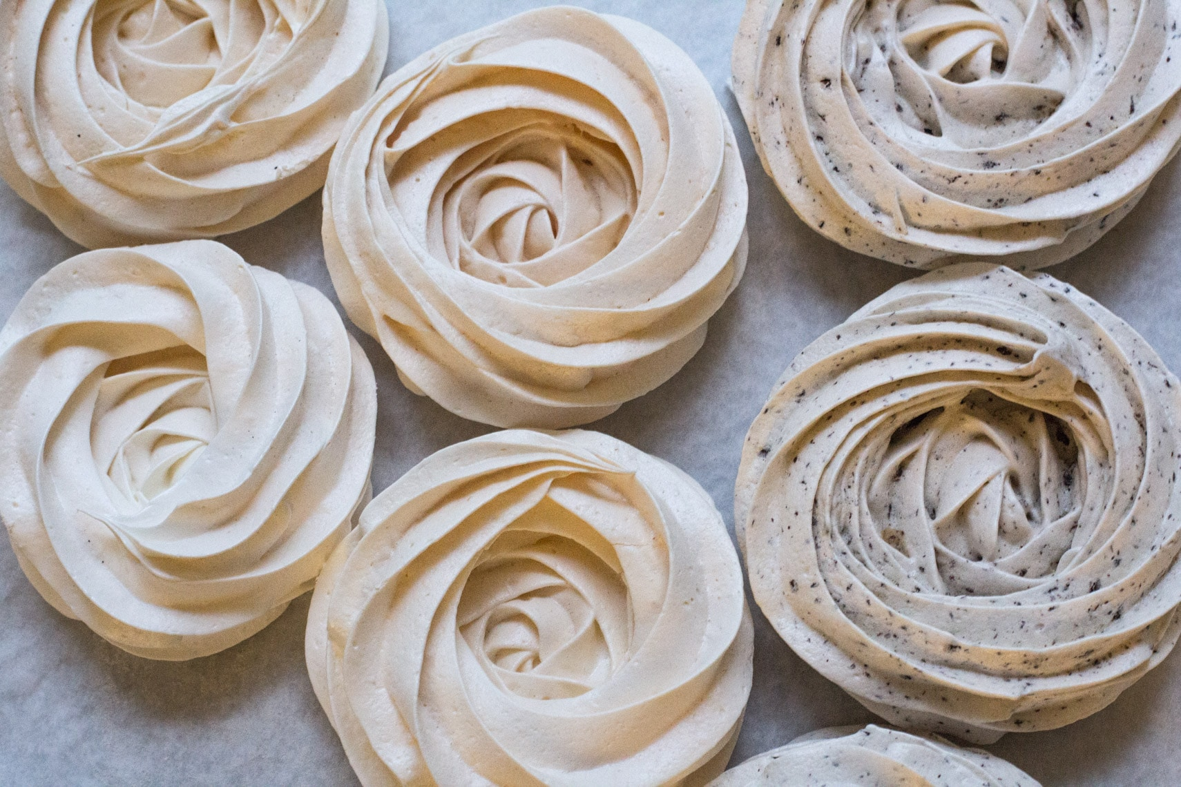 meringue nests piped on a sheet pan with parchment paper