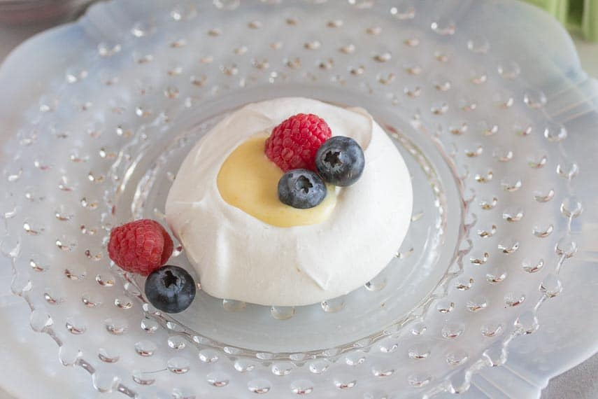 overhead view meringue nests with lemon curd on a glass plate