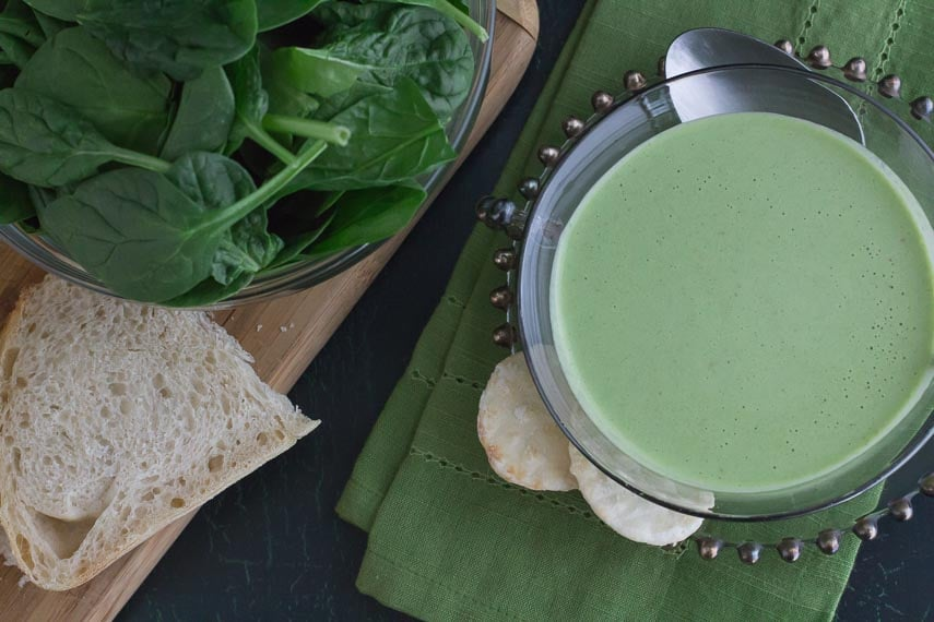 overhead shot of cucumber gazpacho in glass bowl with sourdough bread and spinach alongside as ingredients