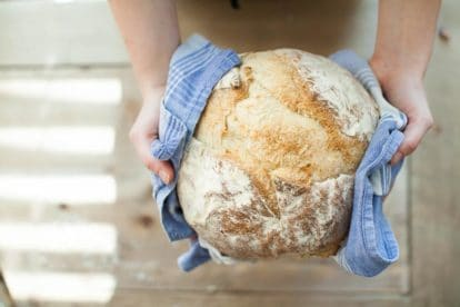 sourdough bread held in hands with a blue kitchen towel