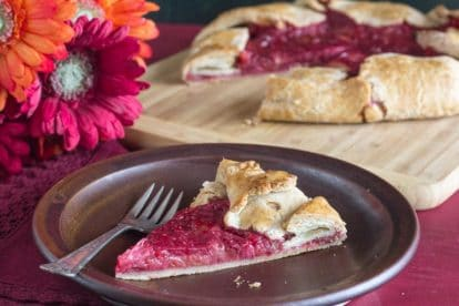 rhubarb raspberry crostata slice on a brown plate with Gerbera daisies in background