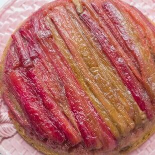 rhubarb upside down cake overhead on a pink platter
