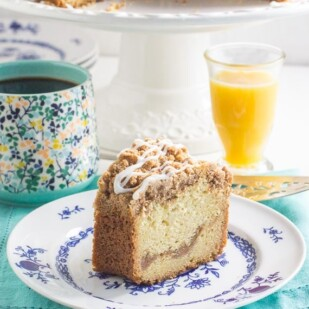 slice of cinnamon streusel coffee cake on a blue and white plate with a glass of orange juice in the background