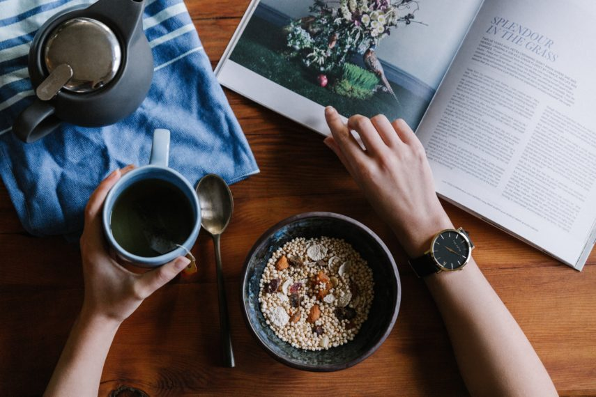 A person sitting reading with a bowl of granola and coffee -The Low FODMAP Diet Elimination Phase: Short & Sweet for Your Health!