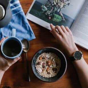 A person sitting reading with a bowl of granola and coffee