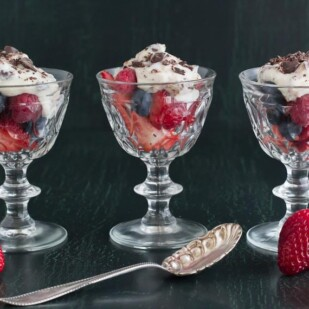 3 glass goblets holding cannoli cream on mixed berries against a dark background