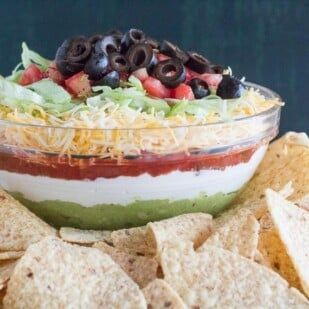 7 layer dip in glass bowl with corn chips in foreground