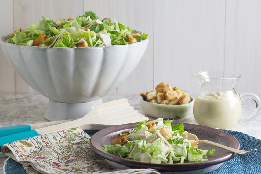 Chopped chicken Caesar salad on brown plate and blue placemat