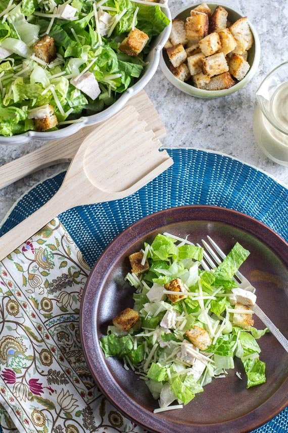 Chopped chicken Caesar salad on brown plate with serving bowl and wooden serving pieces in background