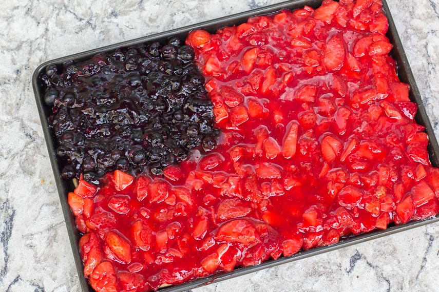 "Flag Slab Pie in a baking pan ready to receive the pastry ""stars and stripes"" against a white and gray quartz background"