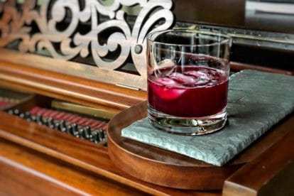 Ginger Beet Old-Fashioned in a clear glass on a piece of slate