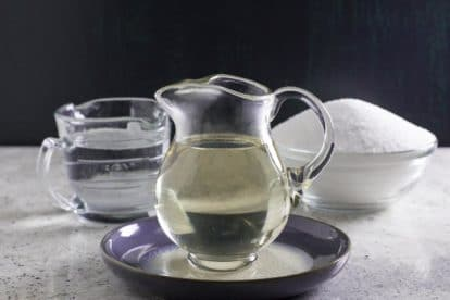 Simple Syrup in clear glass pitcher on blue ceramic dish