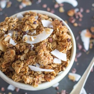 chocolate coconut granola closeup in white bowl with spoon alongside; soft focus background