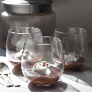 e almond milk pudding with coconut whipped cream in glasses