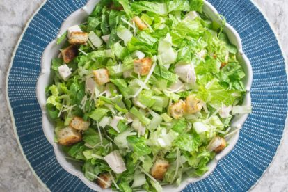 chopped chicken Caesar salad in white serving bowl on round blue placemat