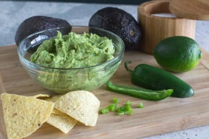 chunky low FODMAP guacamole in a glass bowl on a wooden board, chips alongside