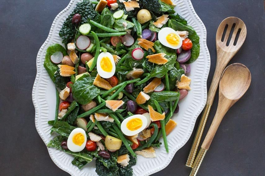 smoked trout Nicoise salad on a decorative white oval platter with wooden serving spoons