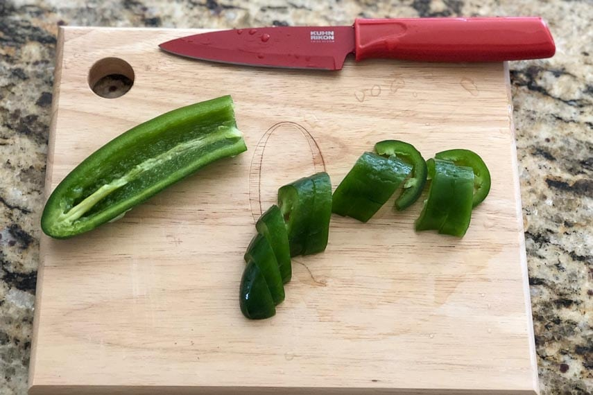 jalapeno being cut on wooden board with red knife; Not a Paloma cocktail