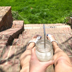 Big Batch Lemonade in a mason jar on a woman's lap