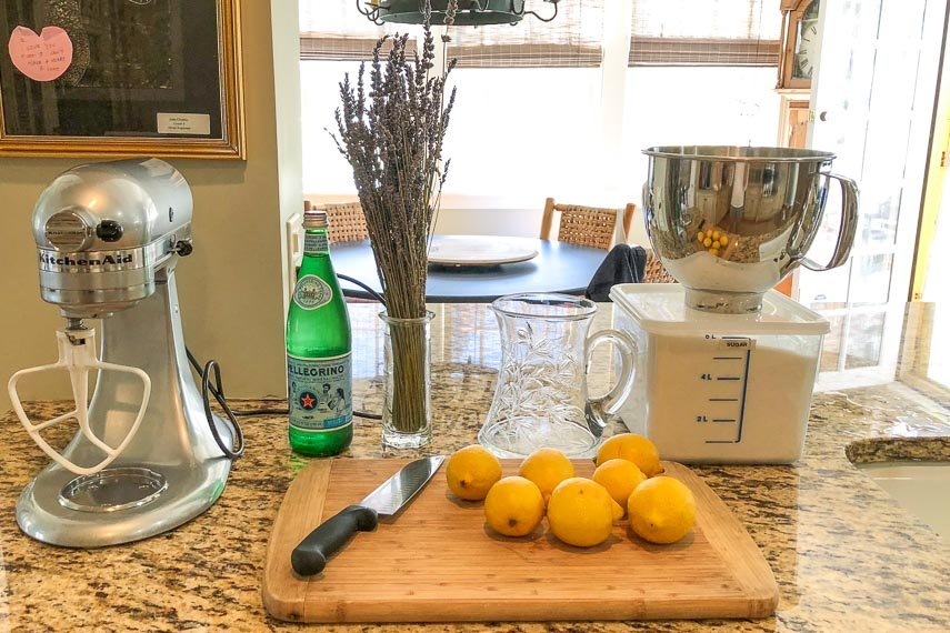 making big batch lemonade with ingredients on counter